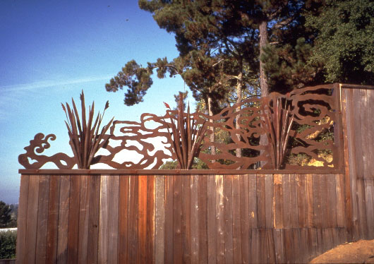 wood fence topped with steel cutouts with Japanese styling